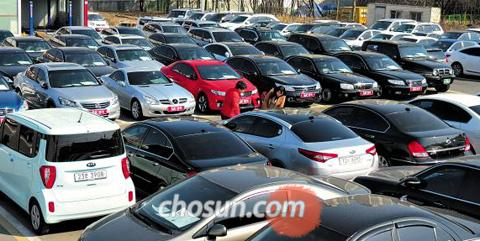 Customers look at used domestic and foreign cars at a used car mart in Ilsan, Gyeonggi Province.
