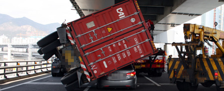 A container trailer lies overturned on a passenger car on Gwangan Bridge in Busan due to typhoon-force winds on Tuesday. /Courtesy of National Police Agency