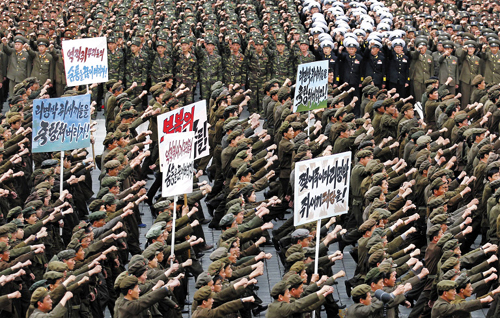 North Koreans march and chant with propaganda boards denouncing South Korean President Lee Myung-bak in Pyongyang on Friday. /AP-Newsis