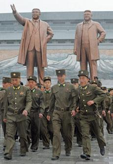 North Korean soldiers walk past bronze statues of North Korea founder Kim Il-sung (left) and late leader Kim Jong-il in Pyongyang on April 25, 2012. /Reuters