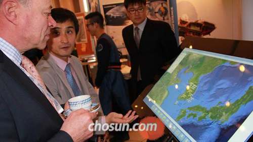 The U.K.s chief delegate (left) listens to a Korean delegates explanation of an electronic map created by the Korea Hydrographic and Oceanographic Administration, which contains only the name