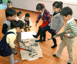 This picture from the official KCNA news agency shows North Korean children attacking a caricature of South Korean President Lee Myung-bak in their classroom in Pyongyang.