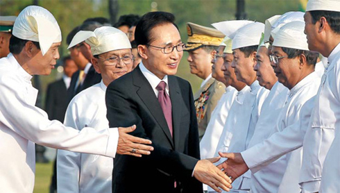 President Lee Myung-bak shakes hands with Burmese officials ahead of the summit with Burmas President Thein Sein in Naypyidaw on Monday. /Yonhap