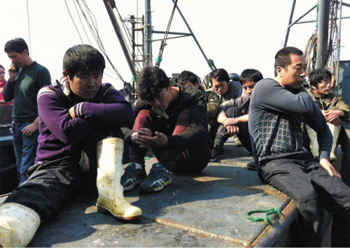 Chinese fishermen, who were held to ransom in North Korea, sit at a pier at Dalian Port in China on Monday. /Courtesy of New Youth Magazine