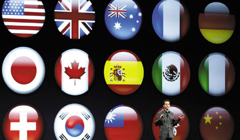 Scott Forstall, Apples senior vice president of iOS Software, shows flags representing different languages for the new iOS 6 software, during the Apple Developers Conference in San Francisco on Monday. /AP-Yonhap
