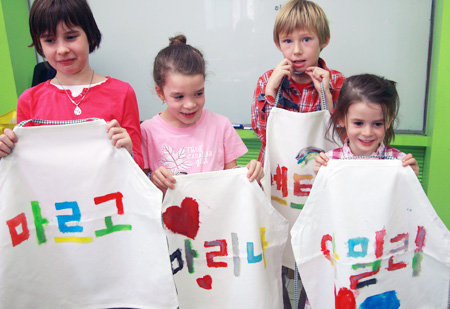 Children show aprons on which they wrote their names in Korean during a class at Seorae Global Village Center in Seoul in May 2012. /courtesy of Seorae Global Village Center