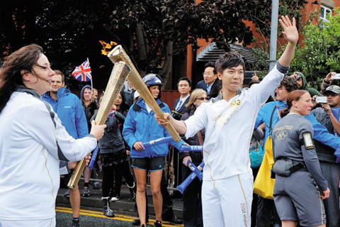 Actor and singer Lee Seung-gi (right) poses with another Olympic torchbearer in Rochdale, the U.K. on Saturday. /Yonhap