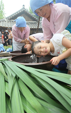 Girls wash their hair in sweet flag water during an event celebrating Dano at the Korean Folk Village in Yongin, Gyeonggi Province on Sunday. /Newsis
