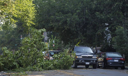 A fallen tree blocks one lane of traffic on 13th Street NW in the Logan Circle neighborhood of Washington on June 30, 2012. /AP