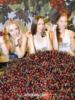 Models show cherries produced in the northwestern U.S. at a department store in Seoul on Monday.