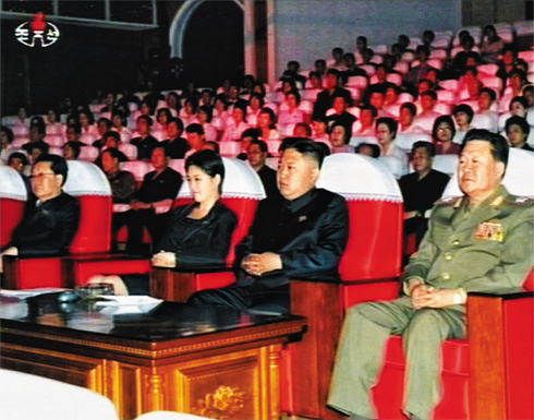 This undated photo released by [North] Korean Central TV shows leader Kim Jong-un and a young woman attending a musical performance. /[North] Korean Central TV-Yonhap
