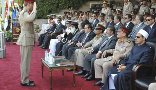 In this image released by the Egyptian President, an Egyptian military officer salutes President Mohammed Morsi (third from right) at a graduation ceremony at a military base east of Cairo, Egypt on July 9, 2012. /AP