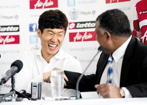 Manchester United midfielder Park Ji-sung (left) shakes hands with Queens Park Rangers chairman Tony Fernandes at a news conference announcing his signing to the London football club on Monday. /AP-Newsis