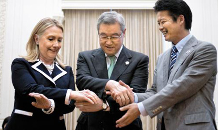 U.S. Secretary of State Hillary Clinton (left) South Korean Foreign Minister Kim Sung-hwan (center) and Japanese Foreign Minister Koichiro Gemba link hands at a meeting on the sidelines of the ASEAN Regional Forum in Phnom Penh, Cambodia on Thursday. /AP-Newsis