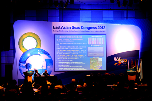 Participants give a presentation during an international conference session.