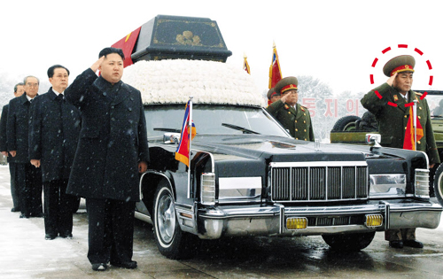 North Koreas leader, Kim Jong-un (front left) salutes beside the hearse carrying the body of his late father Kim Jong-il during the funeral procession in Pyongyang in Dec. 28, 2011. At far right is Ri Yong-ho. /[North] Korean Central TV-Yonhap