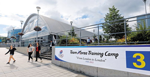 Students walk by a placard at Brunel University, the official Olympic training camp site for the Korean team, in London on Thursday.