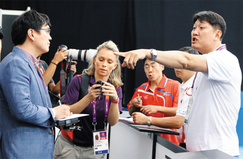 A North Korean table tennis official (right) shouts at South Korean reporters taking photos of players practicing in London on Monday.