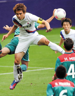 Koo Ja-cheol fights for the ball during Koreas Group B match against Mexico at St. James Park in Newcastle, England on Thursday.
