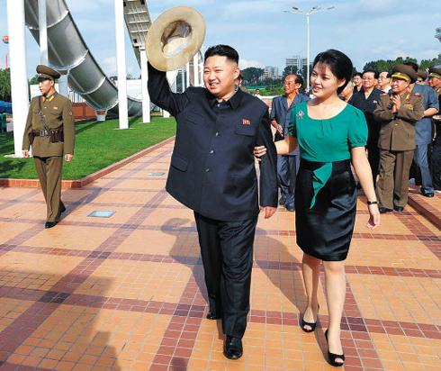 North Korean leader Kim Jong-un walks arm-in-arm with his wife Ri Sol-ju during the completion ceremony of an amusement park in Pyongyang on Wednesday. /[North] Korean Central TV-Yonhap