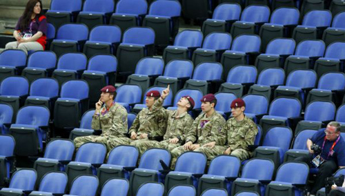 Soldiers sit in the empty seats held by the IOC as they watch the womens gymnastics qualification in the North Greenwich Arena during the London 2012 Olympic Games on July 29, 2012. /Reuters