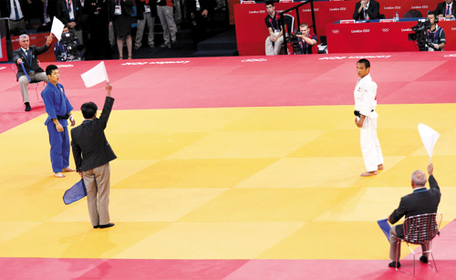 The referee and judges hold up white flags to indicate Japans Masashi Ebinuma (white) as the winner in the mens -66kg quarter-final judo match against Cho Jun-ho (blue) at the London 2012 Olympic Games on Sunday. /Reuters-Yonhap