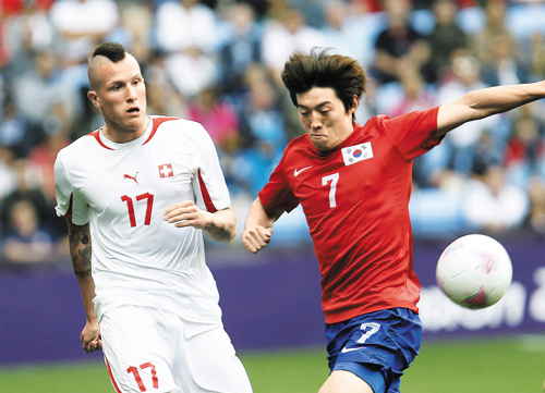 Kim Bo-kyung (right) battles for the ball against Switzerlands Michel Morganella during the Group B soccer match between Korea and Switzerland at the London 2012 Summer Olympics in Coventry, England on Monday. /AP-Newsis