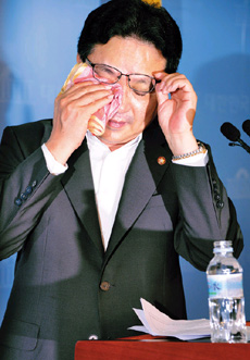 Cho Myong-chol wipes tears during a press conference at the National Assembly on Wednesday.