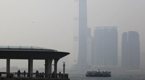 People rest at a ferry pier at the financial central district under hazy weather in Hong Kong on Aug. 1, 2012. In the background, is the citys highest building, the International Commerce Centre in Kowloon peninsula. /Reuters