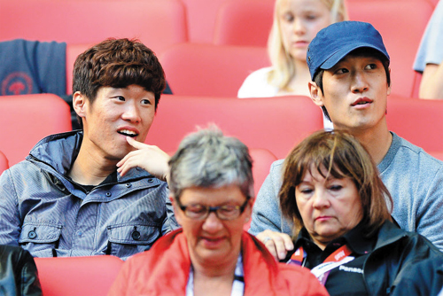 Park Ji-sung and Lee Chung-yong watch the final match of Group B between Korea and Gabon in London on early Thursday.