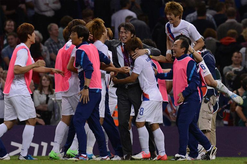 Koreas football team celebrates after beating Great Britain 5-4 in a penalty shootout during the quarterfinals of the Olympic football tournament at Cardiffs Millennium Stadium in Wales early Sunday.