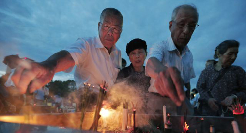 People burn incense and pray in front of the cenotaph dedicated to the victims of the atomic bombing at the Peace Memorial Park in Hiroshima, Japan on Aug. 6, 2012. /AP