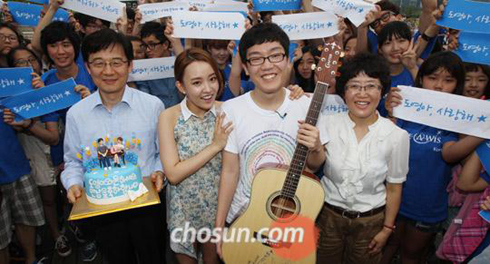 Kim Do-young poses with singer Youn-ha (second left) and a guitar at the Han River Park in Seoul on Thursday.