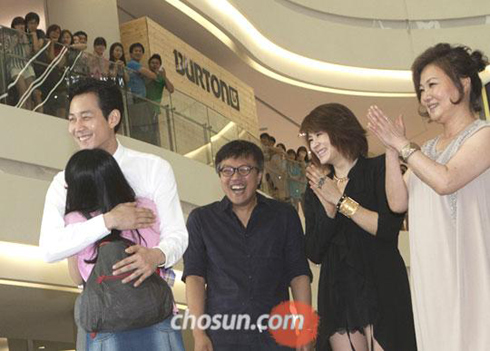 Actor Lee Jung-jae (left) hugs a fan at an event to welcome the 10 millionth viewer of the film