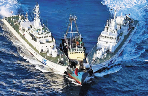 A fishing boat carrying activists from Hong Kong sailing near the disputed islands in the East China Sea, known as Senkaku in Japan or Diaoyu in China, is prevented by the Japan Coast Guards two patrol ships in this handout photo taken by the Japan Coast Guard on Wednesday.