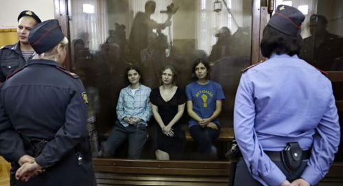 Feminist punk group Pussy Riot members, from left, Yekaterina Samutsevich, Maria Alekhina and Nadezhda Tolokonnikova sit in a glass cage at a courtroom in Moscow, Russia on Aug 17, 2012. /AP
