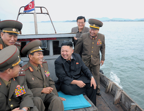 North Korean leader Kim Jong-un smiles in a wooden boat on Friday on his way to the military unit that shelled Yeonpyeong Island in November 2010. /[North] Korean Central News Agency