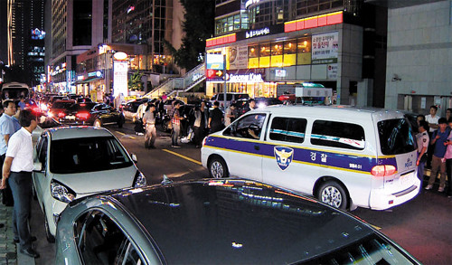 A police vehicle approaches the scene where a man stabbed two former colleagues in Yeouido on Wednesday evening.