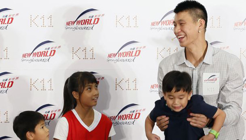 NBA basketball player Jeremy Lin (right) of the Houston Rockets holds up a child during a promotional event in Hong Kong on Aug. 24, 2012. /Reuters