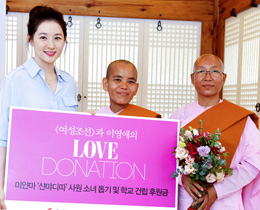 Lee Young-ae poses with monks in Seoul on Monday after making a donation to a Burmese temple. /Courtesy of Woman Chosun