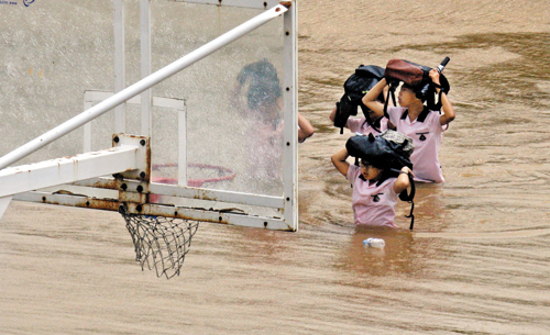 Students cross a submerged basketball court in the aftermath of typhoon Tembin in Mokpo, South Jeolla Province on Thursday. /Newsis