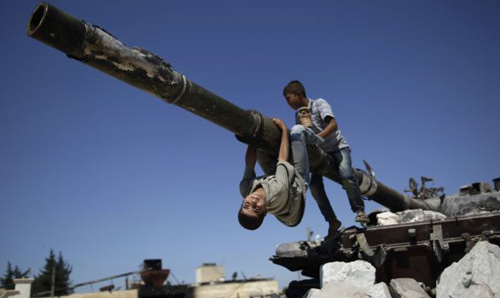 A boy looks back while he and another boy play on a Syrian military tank, destroyed during fighting with the Rebels, in the Syrian town of Azaz, on the outskirts of Aleppo on Sept. 2, 2012. /AP