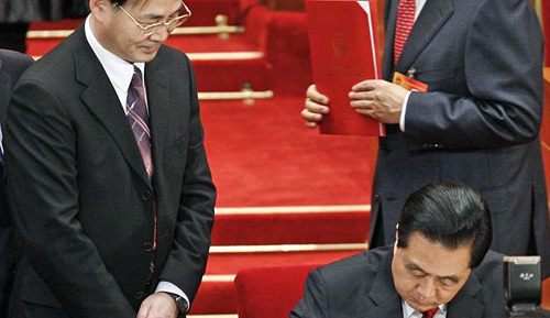 Ling Jihua (left), looks on as Chinese President Hu Jintao signs a document on March 14, 2010. /AP