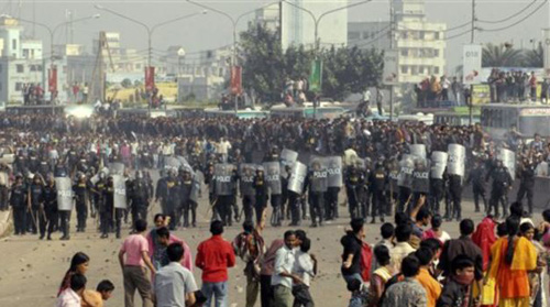 Protesting Bangladeshi garment workers throw stones at police near the international airport in Dhaka, Bangladesh on Dec. 12, 2010. They were demanding the implementation of a new minimum wage. /AP