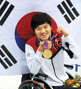 Min Byeong-eon celebrates after receiving the gold in the mens 50-m backstroke at the London Paralympics on Sunday. /Yonhap