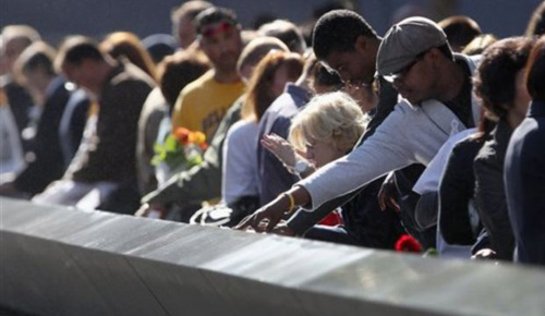 Family members view the names of their relatives etched into the 9/11 Memorial during the commemoration of the 11th anniversary of the terrorist attacks on the World Trade Center in New York on Sept. 11, 2012. /AP