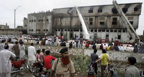 People gather at the site of burnt garment factory in Karachi, Pakistan on Sept. 12, 2012. /AP