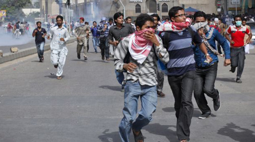 Students run from tear gas fired by police as they tried to march towards the U.S. consulate during an anti-American rally organized by the student wing of religious political party Jamaat-e-Islami, in Karachi, Pakistan on Sept. 17, 2012. /Reuters