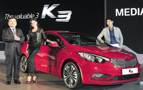 Lee Hyung-geun (left), Kia Motors vice chairman, poses with Kias K3 during the models launch at the Alpensia Resort in Pyeongchang, Gangwon Province on Monday. /Courtesy of Kia Motors