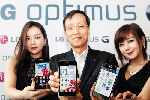 LG Electronics vice president Park Jong-suk (center) shows the Optimus G smartphones at the launch in Seoul on Tuesday.